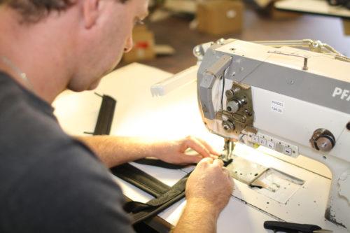 Mann arbeitet an Nähmaschine
