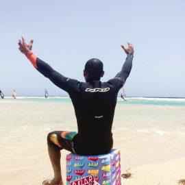 Mann am Strand sitzt auf faltbaren Flatcube