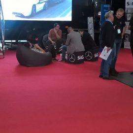 Leute sitzen auf schwarzen Sitzwürfeln und Sitzsäcken auf rotem Teppich