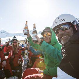 Skifahrer machen Pause auf klappbarem, bedrucktem Sitzwürfel