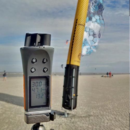 gelb-blaue Airflag am Strand mit Windmessgerät im Vordergrund